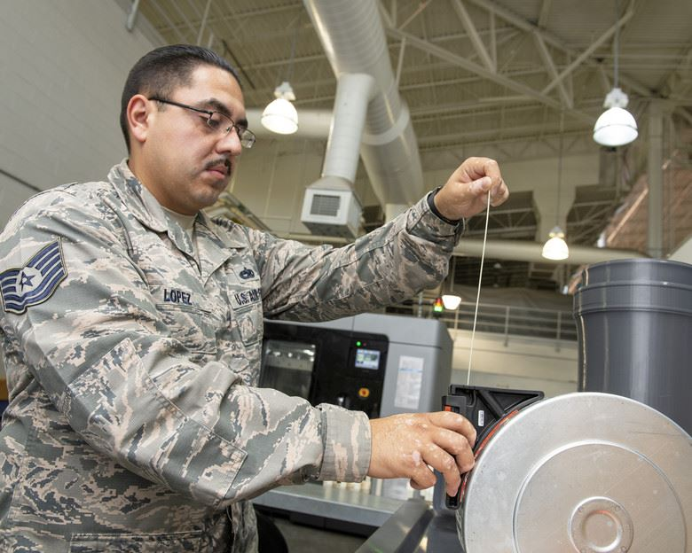 Tech. Sgt. Rogelio Lopez, 60th Maintenance Squadron assistant aircraft metals technology section chief, loads Ultem 9085 material into a canister for use in the Stratasys F900 3D printer, Aug. 15, 2019, Travis Air Force Base, Calif. [Image: U.S. Air Force photo by Louis Briscese]