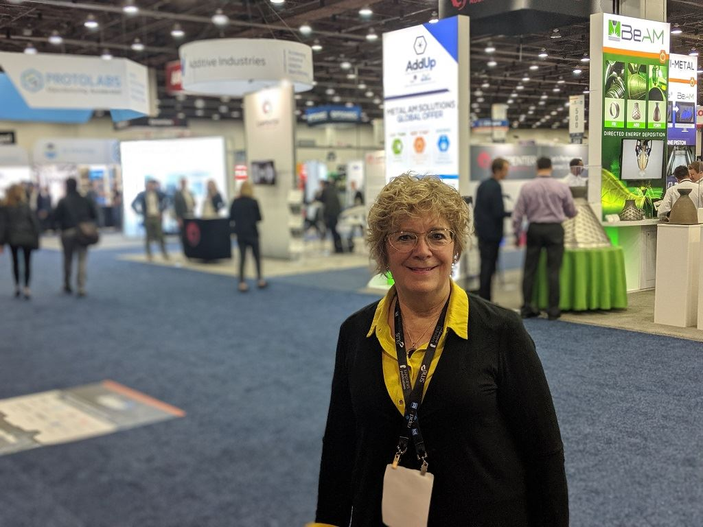 Debra Wilcox, CEO of Accucode 3D, surrounded by 3D printing companies at RAPID + TCT 2019 [Image: Fabbaloo]