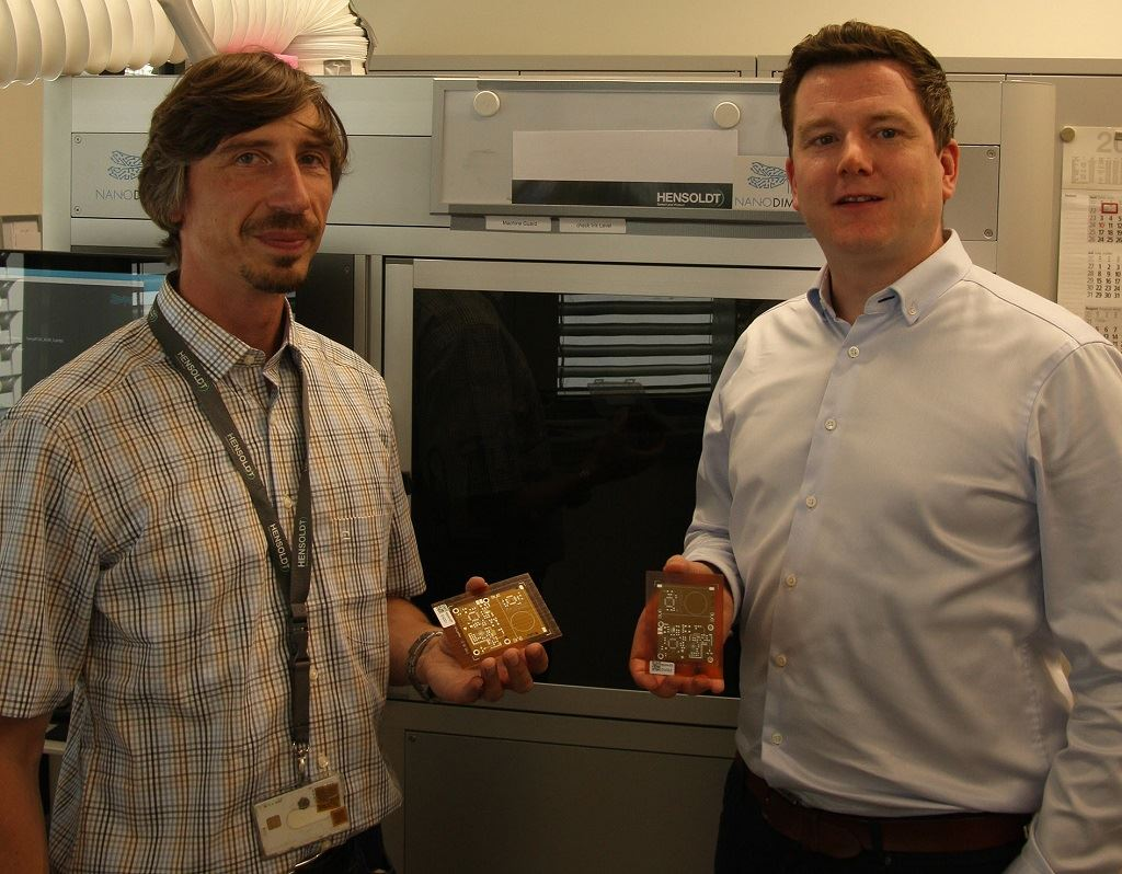 HENSOLDT ALM project manager Andreas Salomon (left) and Nano Dimension's Director Sales EMEA Valentin Storz with first PCB output. [Image: Nano Dimension]