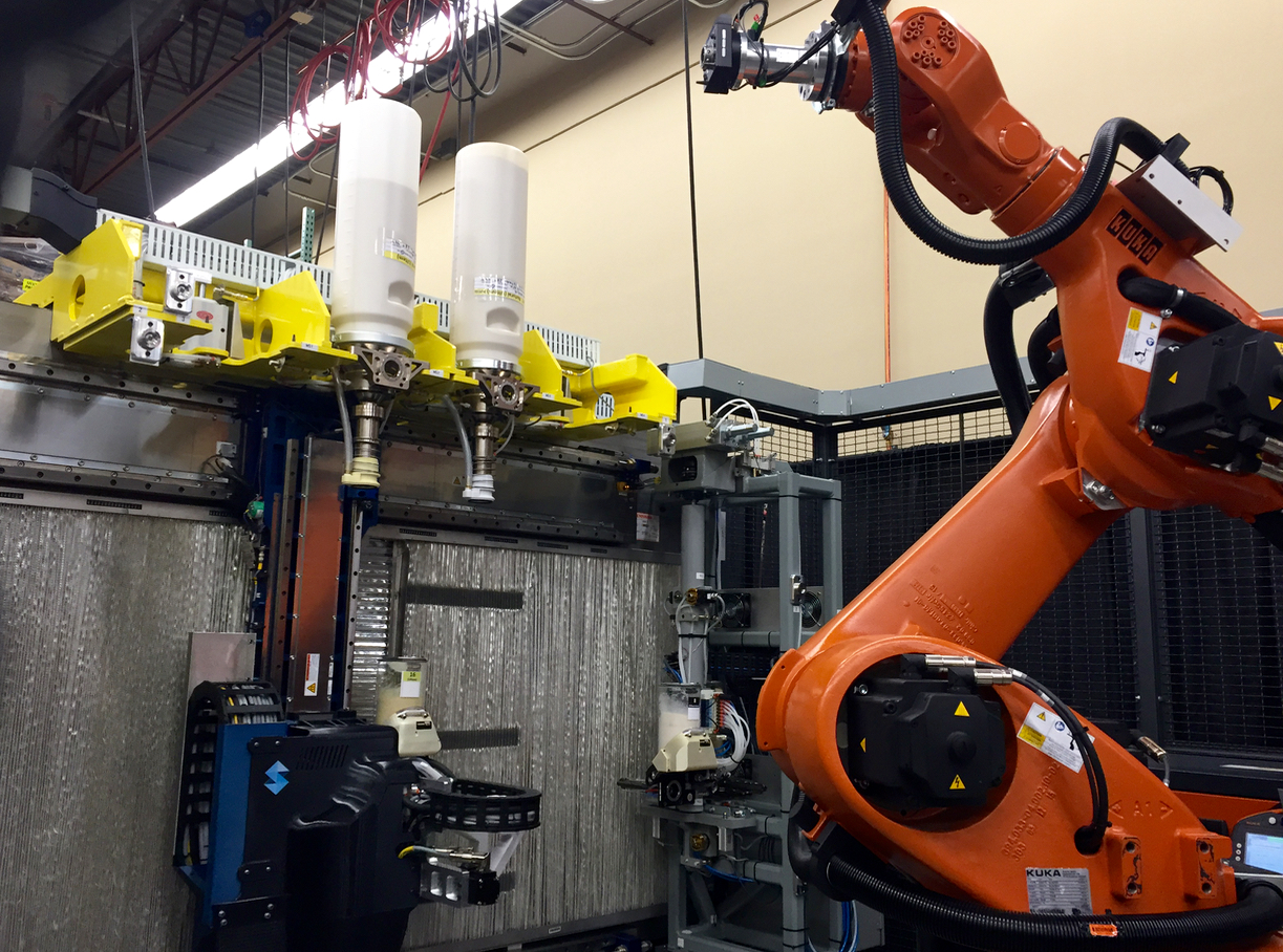 The Stratasys Infinite Build 3D Demonstrator is equipped with a robot arm to quickly swap material cylinders, making this machine multi-material