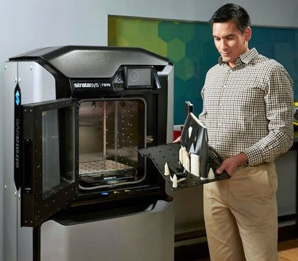 3D printer operator removing completed 3D prints from an F370 device [Source: Stratasys]