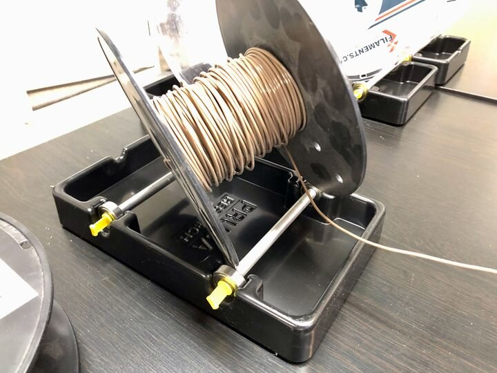 Lightweight filament spool being pulled off the not-so-great Prusa MMU2S spool holders [Source: Fabbaloo]