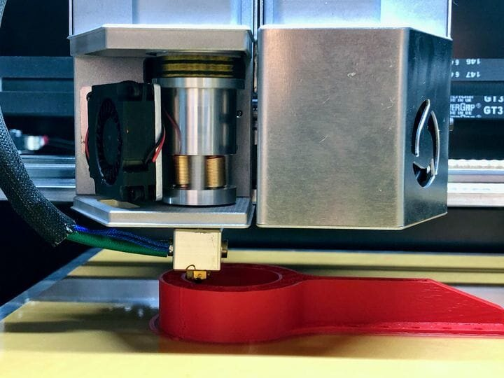 Unique revolving extruder with cover off on the FL300 3D printer. If you look closely you can see two of the three threaded rods around the filament. [Source: Fabbaloo]