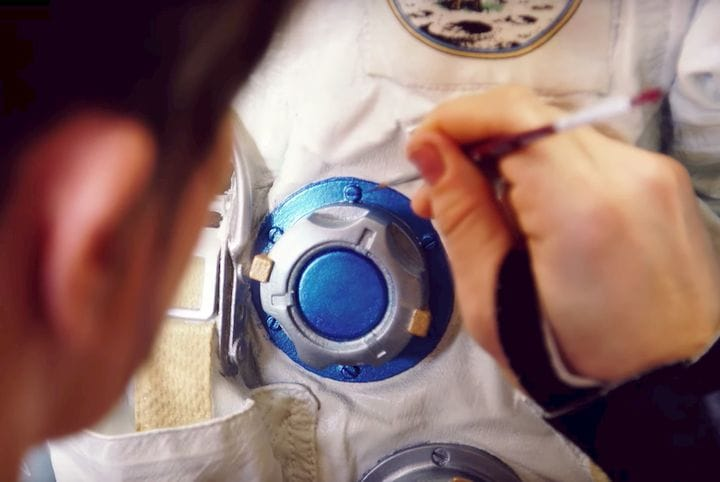Painting a replica of Neil Armstrong's lunar spacesuit [Source: YouTube]