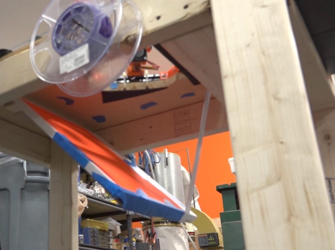 The open trap door allows the 3D print to fall into a bin below the printer