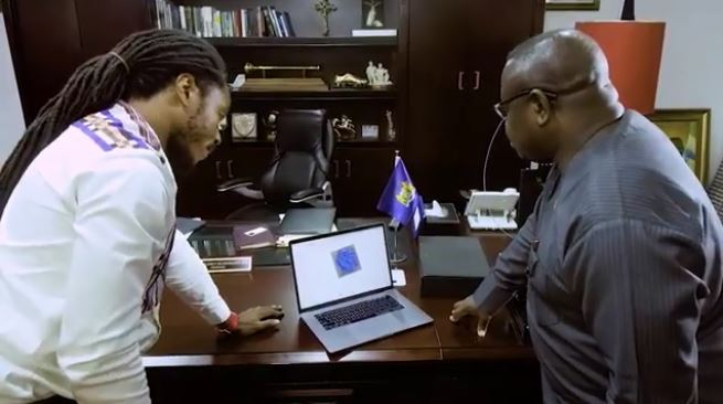 Discussing data over a 3D model in President Bio's office [Image: YouTube]